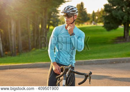 Professional Road Bicycle Racer In Sportswear And Protective Helmet Looking Away While Standing With