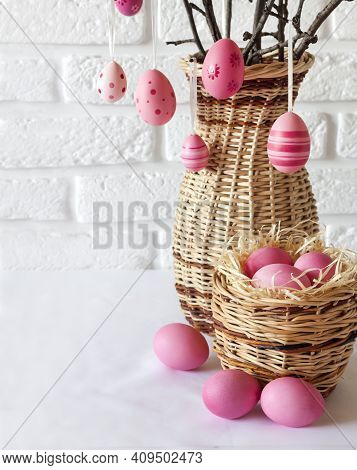 Easter Composition With Decorated Tree Branches In A Wicker Vase And Pink Colored Eggs In Wicker Bas