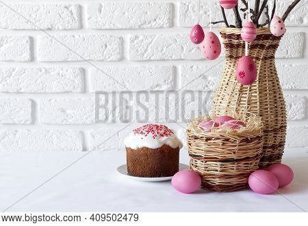 Easter Composition With Decorated Tree Branches In A Wicker Vase, Pink Colored Eggs In Wicker Basket