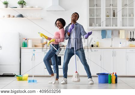Joyful Black Loving Couple Singing Songs While Cleaning Kitchen, Using Broom And Mop As Microphones