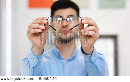 Eyesight And Vision Concept. Closeup Of Unrecognizable Man Showing New Eyeglasses To Camera, Standin