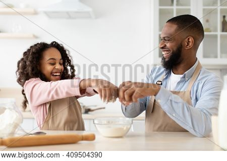 Cooking With Daddy Is Fun. Happy African American Father And His Cute Daughter Making Dough At Kitch