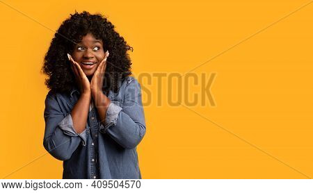 Excited Black Woman Touching Her Face And Looking At Copy Space, Yellow Studio Background, Panorama.