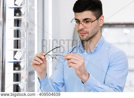 In Optics Shop. Portrait Of Male Client Holding And Wearing Different Spectacles, Choosing And Tryin