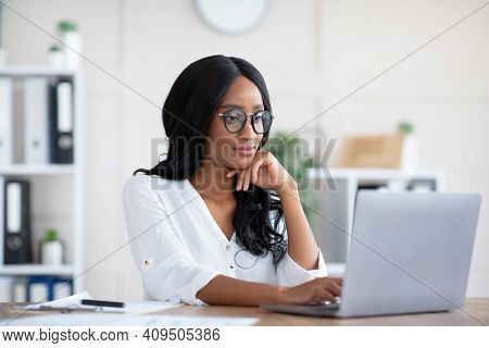 Positive Female Manager Using Laptop Computer At Workplace, Typing Document, Taking Part In Online B