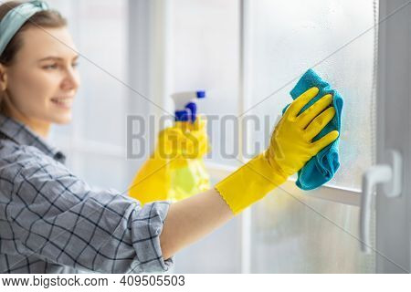Young Housekeeper Washing Window Glass With Rag And Spray Detergent, Selective Focus. Positive Mille