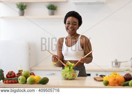 Healthy Diet. African Lady Cooking Salad Slimming At Home, Posing Wearing Fitwear Standing In Modern