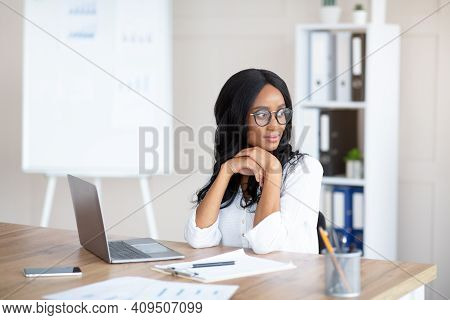 Portrait Of Young Female Secretary Daydreaming In Front Of Laptop At Workplace, Copy Space. Millenni