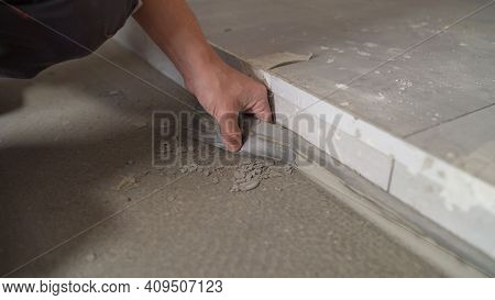 The Worker Glues The Tape To The Floor Around The Room. Construction Concept. Installing Plinth On T