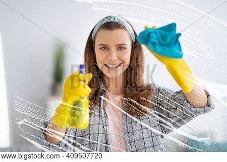 Joyful Young Housemaid Wiping Soap Sud On Glass With Rag, Using Detergent To Wash Window At Home. Lo