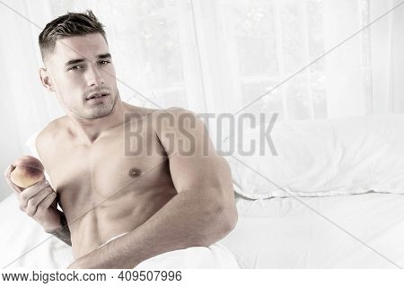 Sexy Muscular Man Lying Shirtless In Bed Revealing Pecs And Sixpack Abs, Holding A Peach And Looking