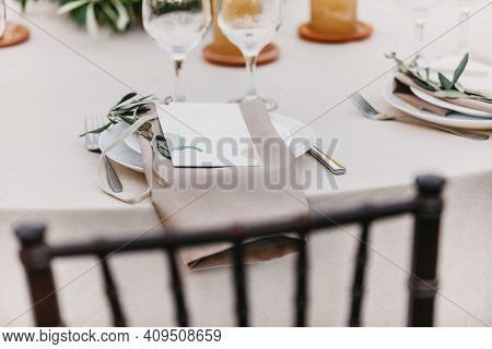 Guest Seat At Party After Wedding Ceremony. Plate, Cutlery, Linen Napkin, Olive Branch, Glasses On G