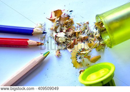 Three Pencils And A Garbage Picker On A White Background