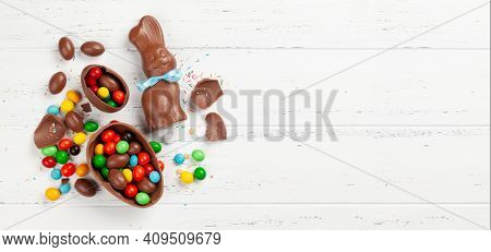Chocolate easter eggs, choco rabbit and colorful sweets on wooden background greeting card. Top view. Flat lay with space for your greetings