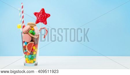 Various sweets assortment. Candy, bonbon, chocolate and macaroons in cocktail glass over blue background. With copy space