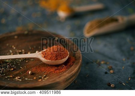 closeup of a wooden spoon full of red curry powder, on a wooden plate, placed on dark stone surface and some other wooden spoons and scoops with different spices and seasonings in the background