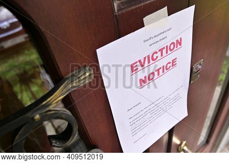 The Notice Of Eviction Of Tenants Hangs On The Door Of The House, Front View