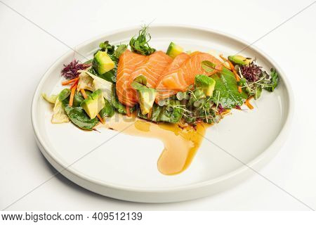 Salmon And Avocado Salad In Tamarind Sauce On A Plate. Ingredients Iceberg Lettuce, Salmon, Avocado,