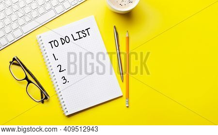Office desk with supplies, coffee and notepad with to do list over yellow. Creativity and inspiration work concept. Top view flat lay with copy space