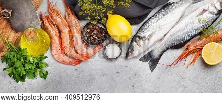 Fresh seafood. Trout fish and langostino shrimps with herbs and spices on a stone background. Top view flat lay