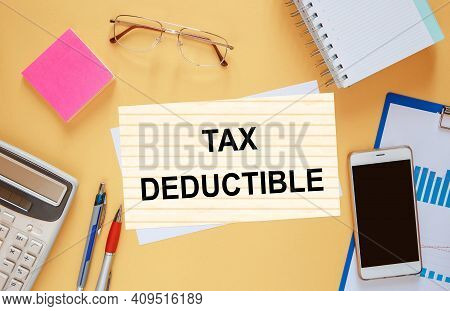 Paper With The Text Tax Deductible On The Office Table Among The Stationery.