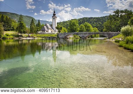 View Of The Church Of St. John The Baptist On The Banks Of The Sava River Near Lake Bohinj In Sloven