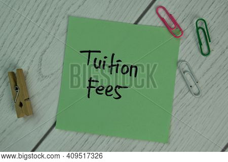 Tuition Fees Write On Sticky Notes Isolated On Wooden Table.