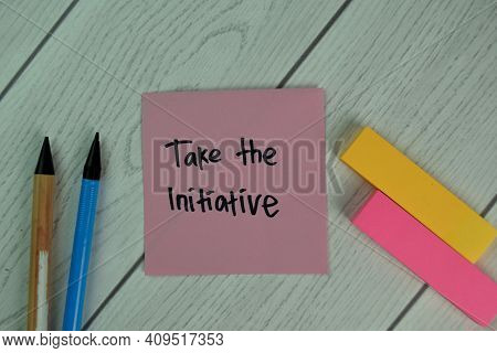 Take The Initiative Write On Sticky Notes Isolated On Wooden Table.