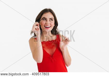 Smiling beautiful caucasian girl posing with mascara isolated over white background