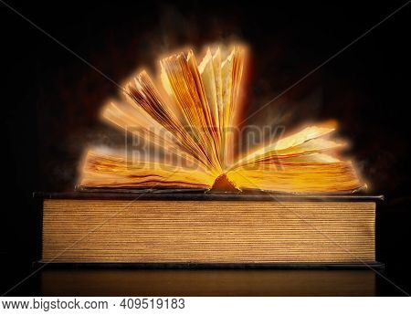 Open Old Vintage Book On Black Background, Golden Haze Around