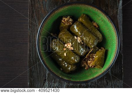 Dolmas - Stuffed vine leaves with rice in a bowl. Top view. Food photo of delicious Mediterranean food.