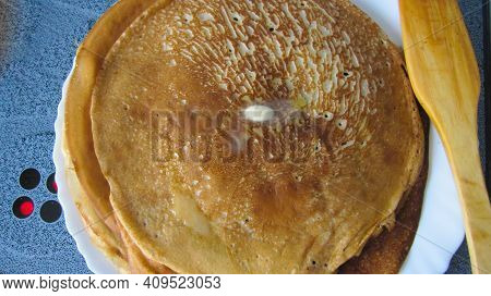 Russian Pancakes Are Stacked, A Piece Of Butter Melts On Top. Spring Festival Maslenitsa.