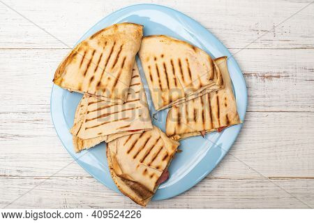 Pita, Tortilla With Cheese And Ham On A Plate On A White Wooden Background. A Light, Healthy Snack.