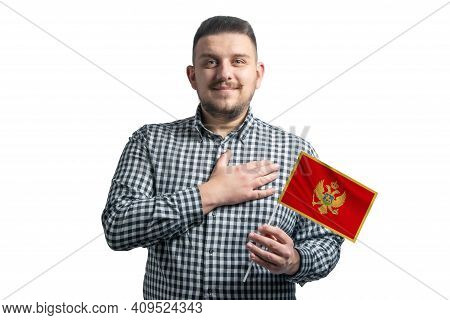 White Guy Holding A Flag Of Montenegro And Holds His Hand On His Heart Isolated On A White Backgroun
