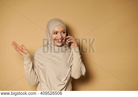 Attractive Arab Woman With Beautiful Toothy Smile And Covered Head Talking On Mobile Phone Standing