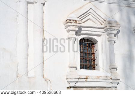 Arched Window In A White-stone Brick Wall With An Openwork Arch In The Form Of A Cross