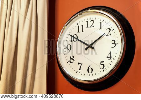 Classic Round Wall Clock In The Interior With Arabic Numerals, White Dial And Black Hands. Against T