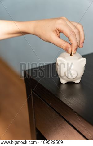 Child's Hand Putting A Coin Into A Piggy Bank. Earnings, Saving And Finance Concept