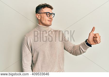Hispanic young man wearing casual turtleneck sweater looking proud, smiling doing thumbs up gesture to the side