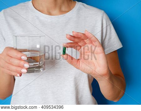 The Medicine. The Woman Takes A Pill. Tablet And Glass Of Water In Female Hands On A Blue Background