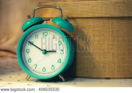 Vintage Image Of Old Alarm Clock On Background Of Wicker Straw Hat Box. Interior Decorative Elements