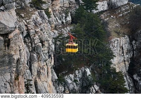 Cabin Of The Aerial Tramway Moves Against The Background Of A Steep Rocky Cliff