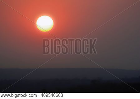 White Hot Sun And Red Sky At Sunset. Landscape With A Solar Disk Above The Ground In The Smoke Of Wi