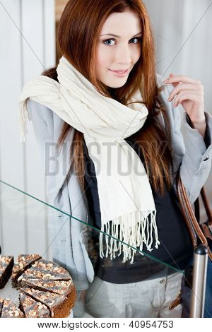 Lady in scarf looking at the bakery window full of different pieces of tarts