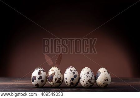 Quail Egg Easter Bunny And A Row Of Quail Eggs On A Brown Background. Egg With Bunny Ears, Easter Ba
