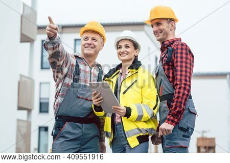 Builder and contractor inspecting new houses and residential buildings on construction site