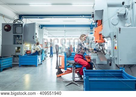 Woman worker in factory producing metal parts on punching machine