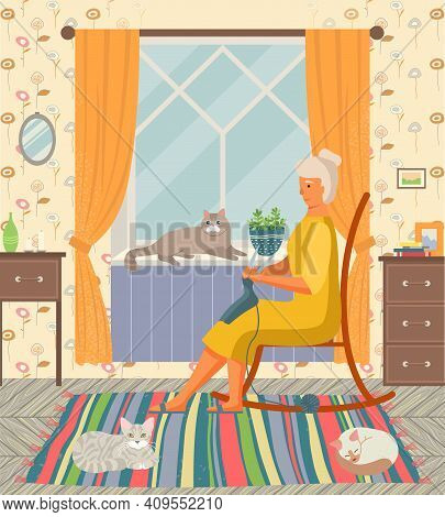 Grandma Knitting In Her Rocking-chair, Sitting At Home With Her Cats In Cozy Room Interior At The Wi