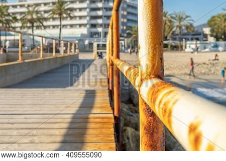 Close-up Of A Rusty Metal Railing In The Harbor Of Magaluf Beach, Island Of Mallorca. In The Backgro