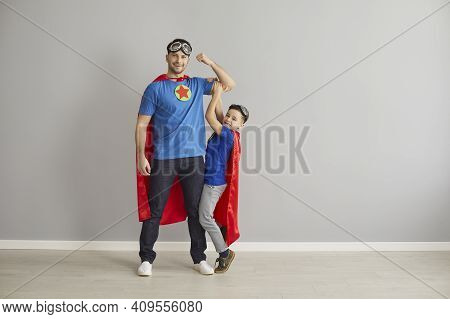 Happy Young Dad And Little Son Dressed In Hero Capes Playing And Having Fun Together